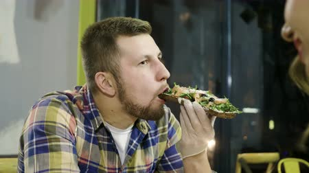 バゲット : Young bearded man eating an open sandwich with rye bread, salted salmon, cheese, vegetables and herbs. 4K