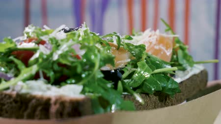 omega : Close-up shot of an open sandwich with rye bread, salted salmon, cheese, vegetables and herbs. 4K Stock Footage