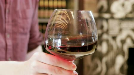 goblet : Barman at work. Male hand stirring a wine glass with red wine in it. 4K