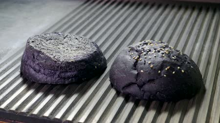american cuisine : Black bun. Close-up shot of two halves of hamburger bread are being fried on a grill for burger. 4K