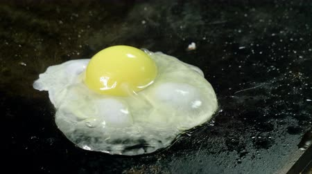 omlet : Close-up shot of cook breaking the egg and frying it on a hot oiled grill. 4K Stok Video