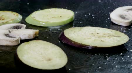 beringela : Close-up shot of the cook frying slices of zucchini, eggplant, champignon on grill. 4K Stock Footage