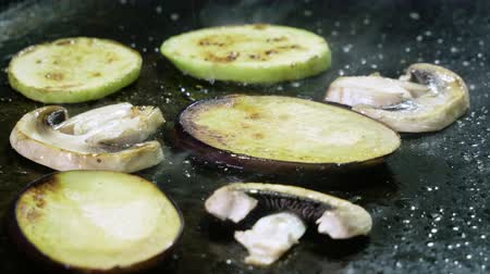 eggplant : Close-up shot of slices of zucchini, eggplant, champignon being fried on grill. 4K Stock Footage