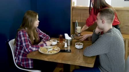 gruel : Teenage boy and girl eating breakfast food and drinking soft drinks in a cafe 4K