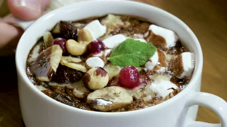 gruel : Close-up of oatmeal porridge with nuts, berries, banana, chocolate served for breakfast in a restaurant. 4K