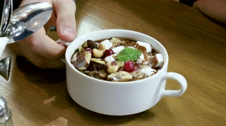 edények : Close-up of oatmeal porridge with nuts, berries, banana, chocolate served for breakfast in a restaurant. 4K
