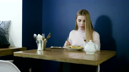 viennese : Young blonde girl eating waffles for breakfast, drinking tea and taking notes in notepad. 4K