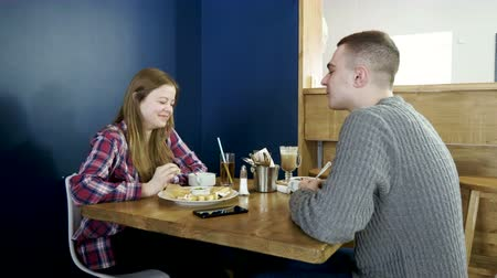 zabkása : Teenage boy and girl eating breakfast food and drinking non-alcoholic beverages in a restaurant. 4K