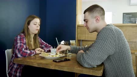 mush : Teenage boy and girl eating breakfast food and drinking soft drinks in a cafe 4K