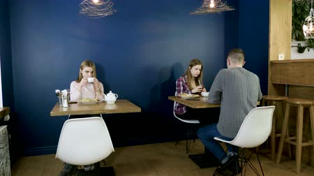 оладья : Two teenage girls and guy eating food, drinking drinks in the modern cafe. 4K