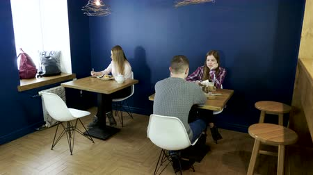 eaten : Two teenage girls and guy eating food, drinking drinks in the modern cafe. 4K