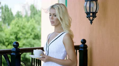 mole : Beautiful young blonde woman in white dress drinking a cup of tea, standing on the balcony of a luxury hotel. 4K Videos