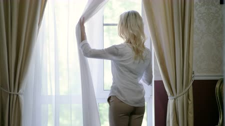 repouso : Attractive young blonde woman opening curtains, looking at window in home. 4K