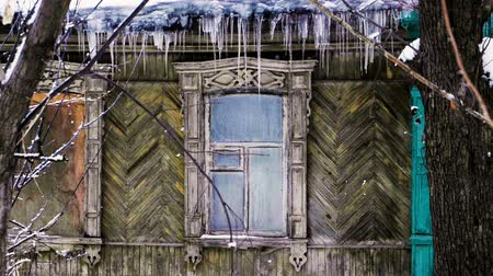 rampouch : Exterior of old wooden house with icicles hanging on the roof. Slow motion. HD Dostupné videozáznamy