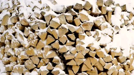 sawn : Wooden background. Close-up shot of pile of wood logs covered with snow. Slow motion. HD Stock Footage