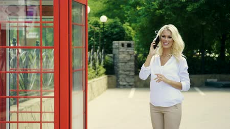 telefooncel : Young beautiful blonde woman smiling, waving her hand, talking on the phone next to the red telephone booth. 4K Stockvideo