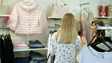 nőiesség : Two happy young girls are choosing clothes in a department store. 4K