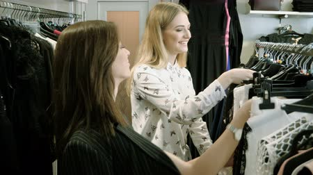 потребитель : Two happy young girls are choosing clothes in a department store. 4K