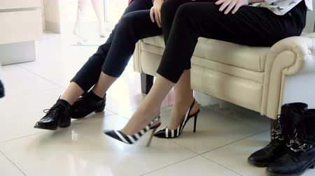 high heel shoe : Close-up of young pretty woman trying on womens shoes with high heels in shop. 4K