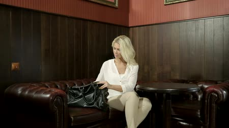 vendég : Young beautiful blonde woman sitting with womens black bag on leather sofa in hotel lobby. HD