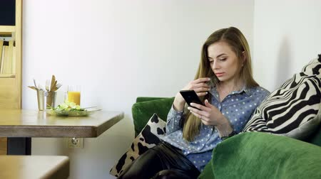 беспроводной : Attractive young happy woman using mobile phone during resting in a cafe. 4K