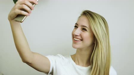 hippi : Beautiful blonde woman looking at her cell phone and taking a selfie in a modern cafe. 4K Stock mozgókép