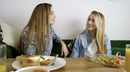 ajánlás : Two beautiful women sitting at the cafe, chatting and having fun together. 4K