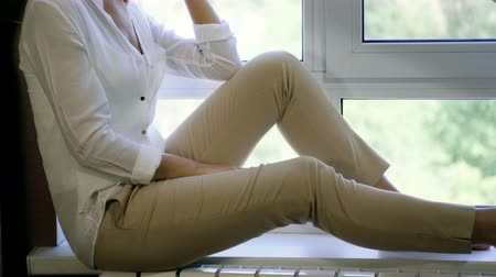 trousers : A young woman sitting on the windowsill and looking thoughtfully out the window. 4K