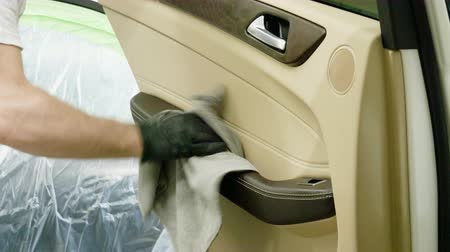 detailing : Male hand cleaning the door panel with microfiber cloth at car interior. 4K