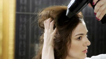 shaping : Attractive young woman dressed in bathrobe drying dark long hair with a hair dryer in bathroom at home. Slow motion. HD