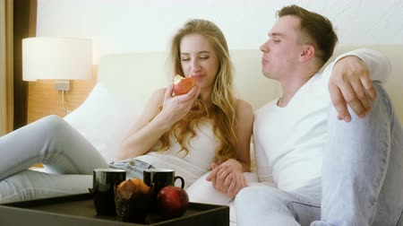 casal : Young lovers man and woman having breakfast in bed: drinking tea or coffee, eating pastries and apples in the bedroom. 4K Stock Footage