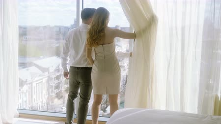 hotel suite : Young woman and man enjoying their suite, hugging and kissing at honeymoon vacation. 4K