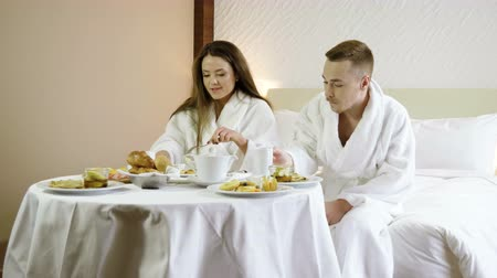 медовый месяц : Loving couple enjoying healthy breakfast, sitting on the bed at luxury hotel. 4K