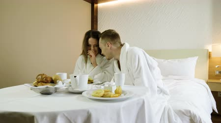 медовый месяц : Young couple dressed in white bathrobes enjoying breakfast eating croissants, drinking hot tea, talking and laughing in bedroom at luxury hotel. 4K