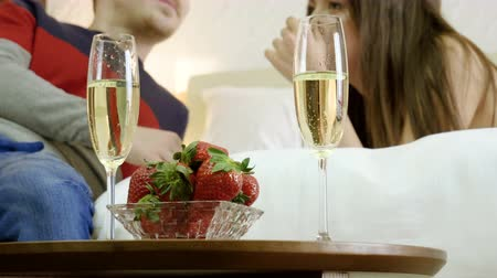 медовый месяц : Young happy man and woman drinking champagne, eating fresh strawberries, talking, smiling, laughing on the bed. 4K