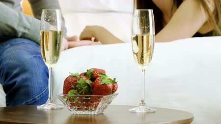 resting : Young happy man and woman drinking champagne, eating fresh strawberries, talking, smiling, laughing on the bed. 4K