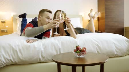 quarto : Young happy man and woman drinking champagne, eating fresh strawberries, talking, smiling, laughing on the bed. 4K