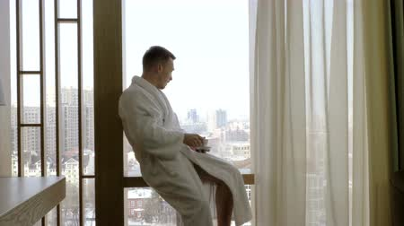 agglegény : Handsome man dressed in white bathrobe drinking coffee and looking out of the window at home. 4K