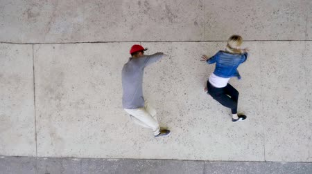 breakdancing : Street dance. Top view of young couple of professional dancers dancing, breakdancing and performing freestyle dance. Slow motion. HD