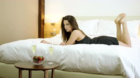 pezsgő : Beautiful brunette woman dressed in nightie lying in bed waiting her boyfriend for drinking champagne and eating strawberries. 4K