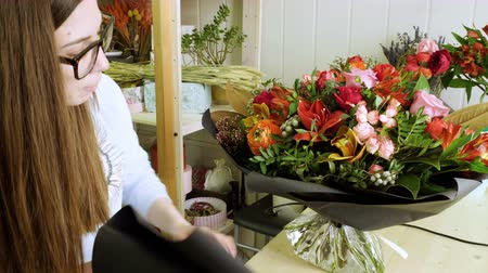 floral composition : Female florist in flower shop. Woman making a beautiful and stylish bouquet of fresh flowers in floral design studio. 4K Stock Footage