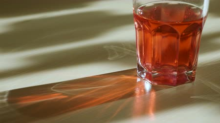 odrážející : Play of light. Close-up of the glass with a red drink through which passing the rays of light and reflecting glare on the table. 4K