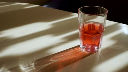 spektrální : Play of light. Close-up of the glass with a red drink through which passing the rays of light and reflecting glare on the table. 4K