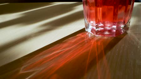 kompot : Play of light. Close-up of the glass with a red drink through which passing the rays of light and reflecting glare on the table. 4K