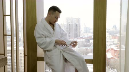 venda : Handsome man dressed in white bathrobe sitting on the windowsill and using tablet computer. 4K