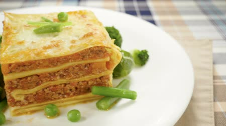 lasagne : Italian food. Close-up shot of meat lasagna on a white plate. Slow motion. HD