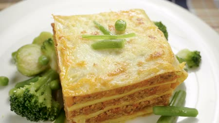 green peas : Italian food. Close-up shot of meat lasagna on a white plate. Slow motion. HD