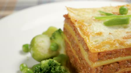 peas : Italian food. Close-up shot of meat lasagna on a white plate. Slow motion. HD