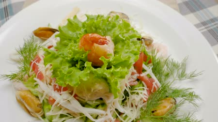 shellfish dishes : Healthy salad with mussels, shrimps, squid, lettuce, tomatoes, cucumber, apple, cheese. Slow motion. HD