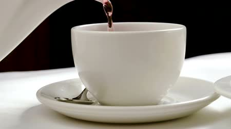 bica : Tea being poured into a tea cup. Close-up shot of ceramic teapot and teacup. Slow motion. HD